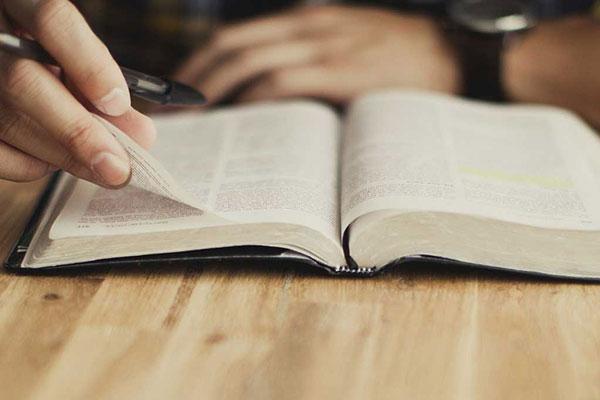 homem lendo bíblia em cima da mesa com caneta