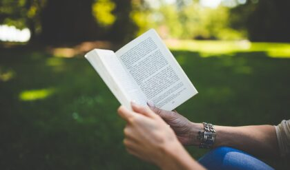 mãos de uma pessoa segurando livro cristão em um jardim verde